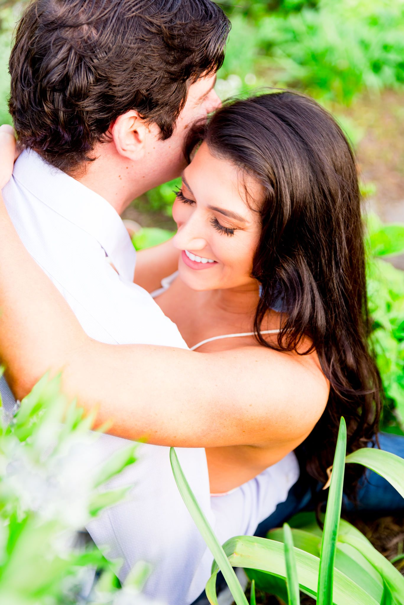 woman with long dark hair hugging fiance and smiling with eyes closed in Lincoln Park gardens
