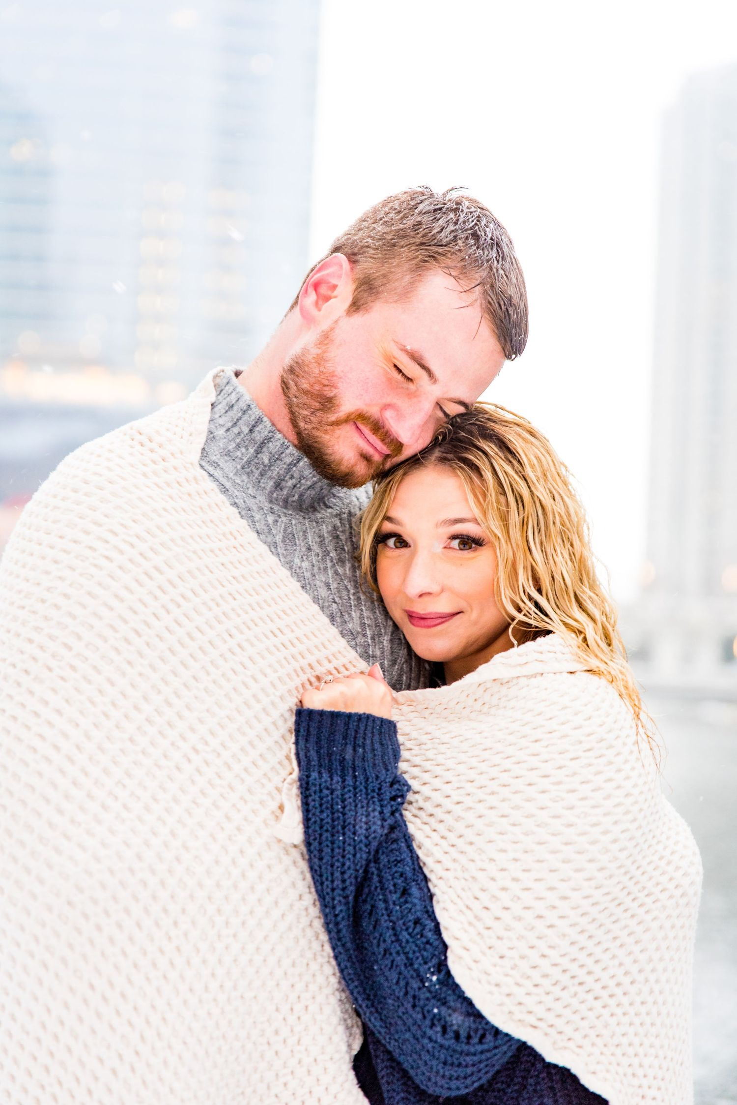 engaged couple wrapped in blanket for snowy Chicago engagement pictures at Wolf Point and Merchandise Mart