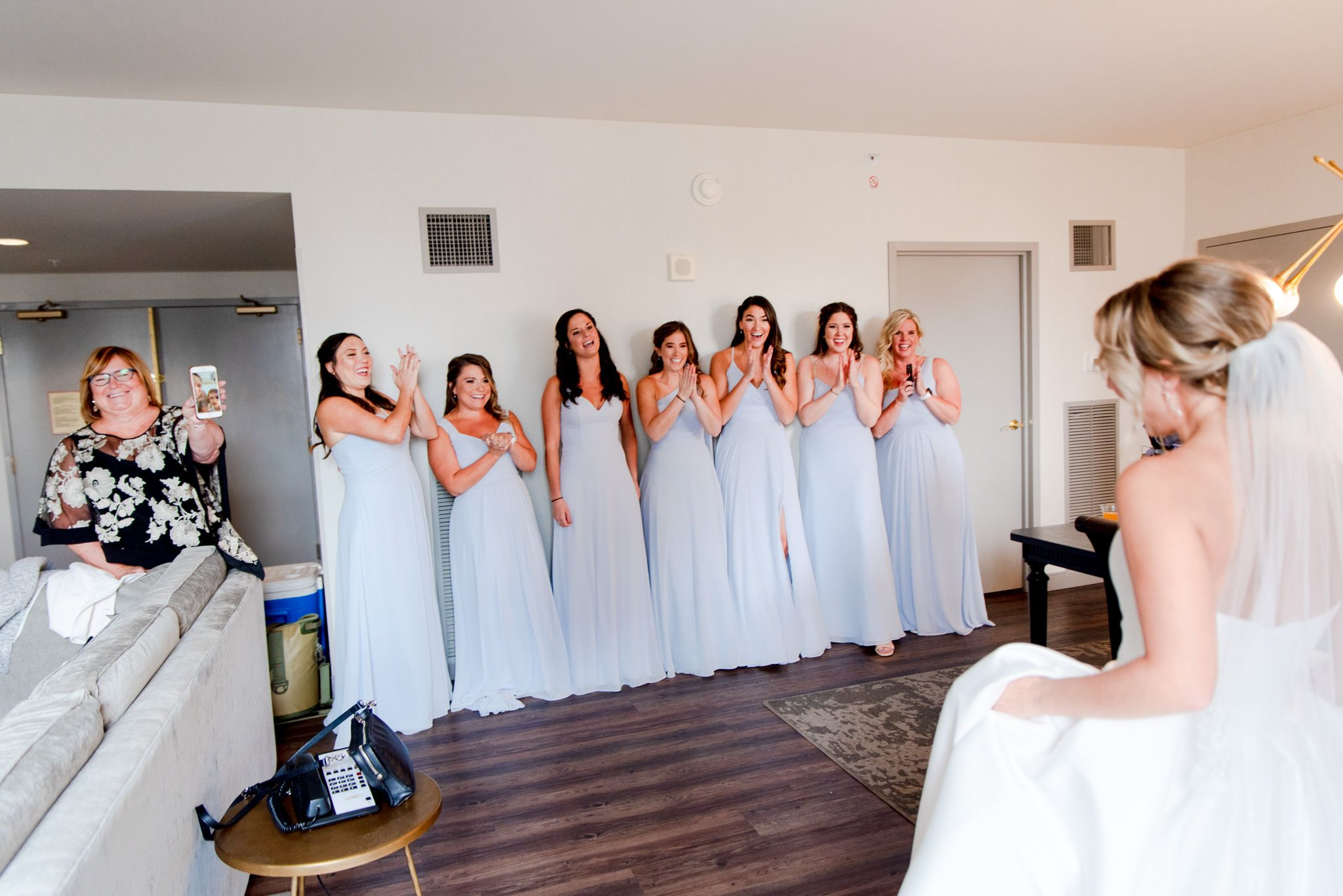 7 bridesmaids in light blue dresses smiling and clapping after seeing the bride, while mom smiles and holds up phone