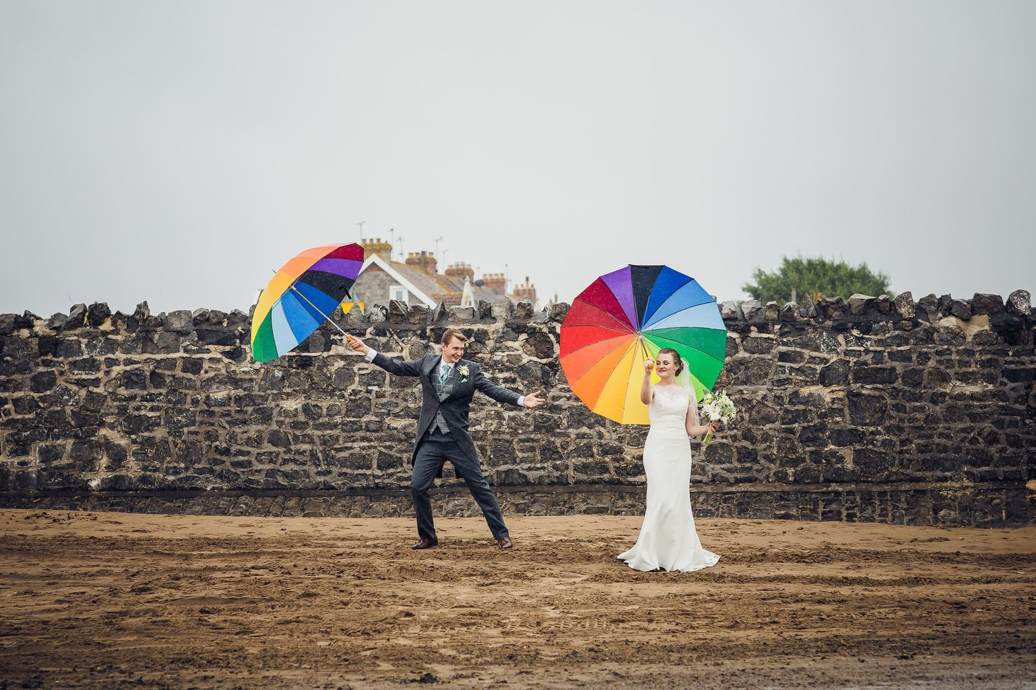 bride and groom dancing with rainbow umbrellas in the rain