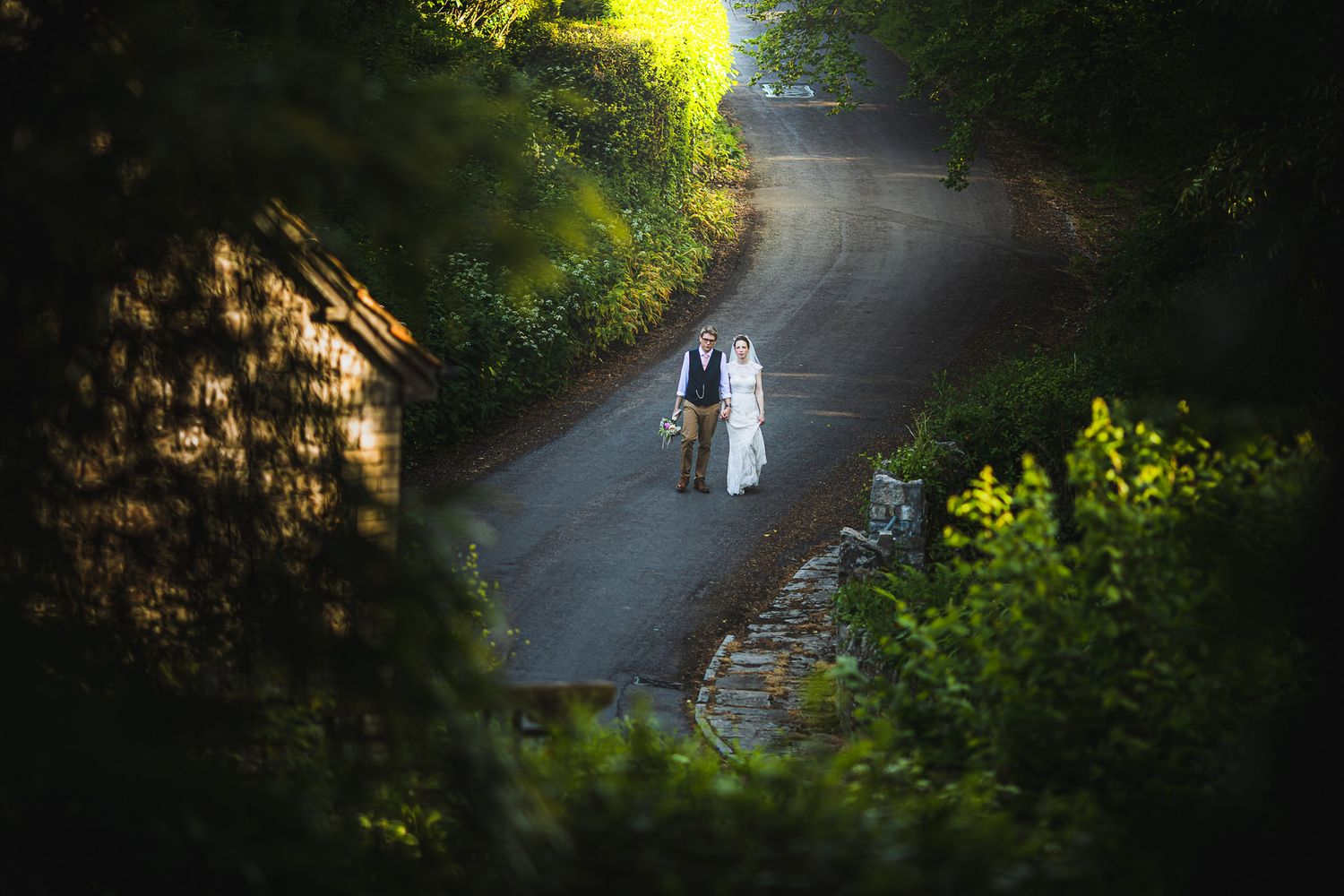 bride and groom walking along quiet country road