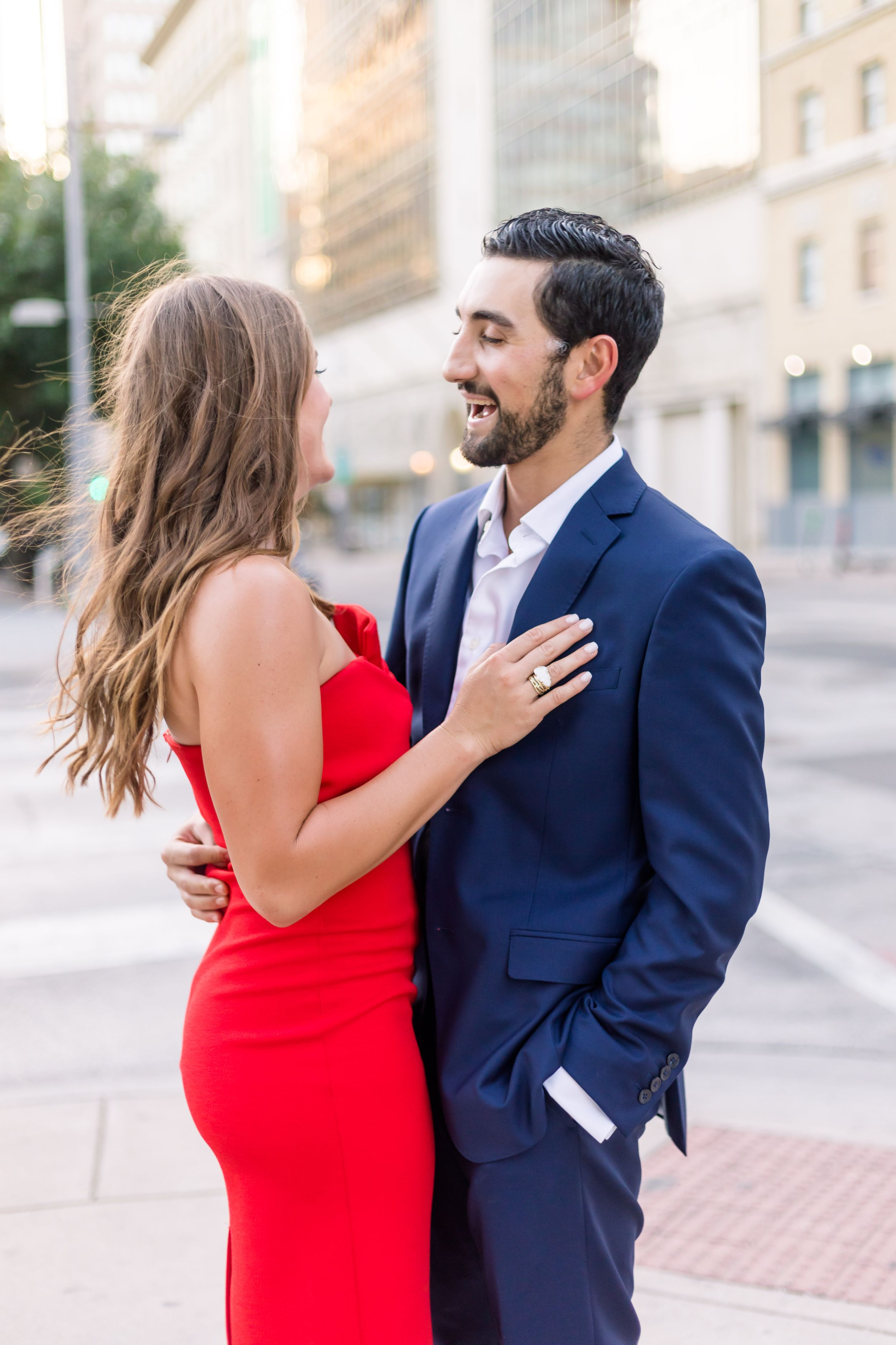 A couple laughs together for portraits in Downtown Dallas.