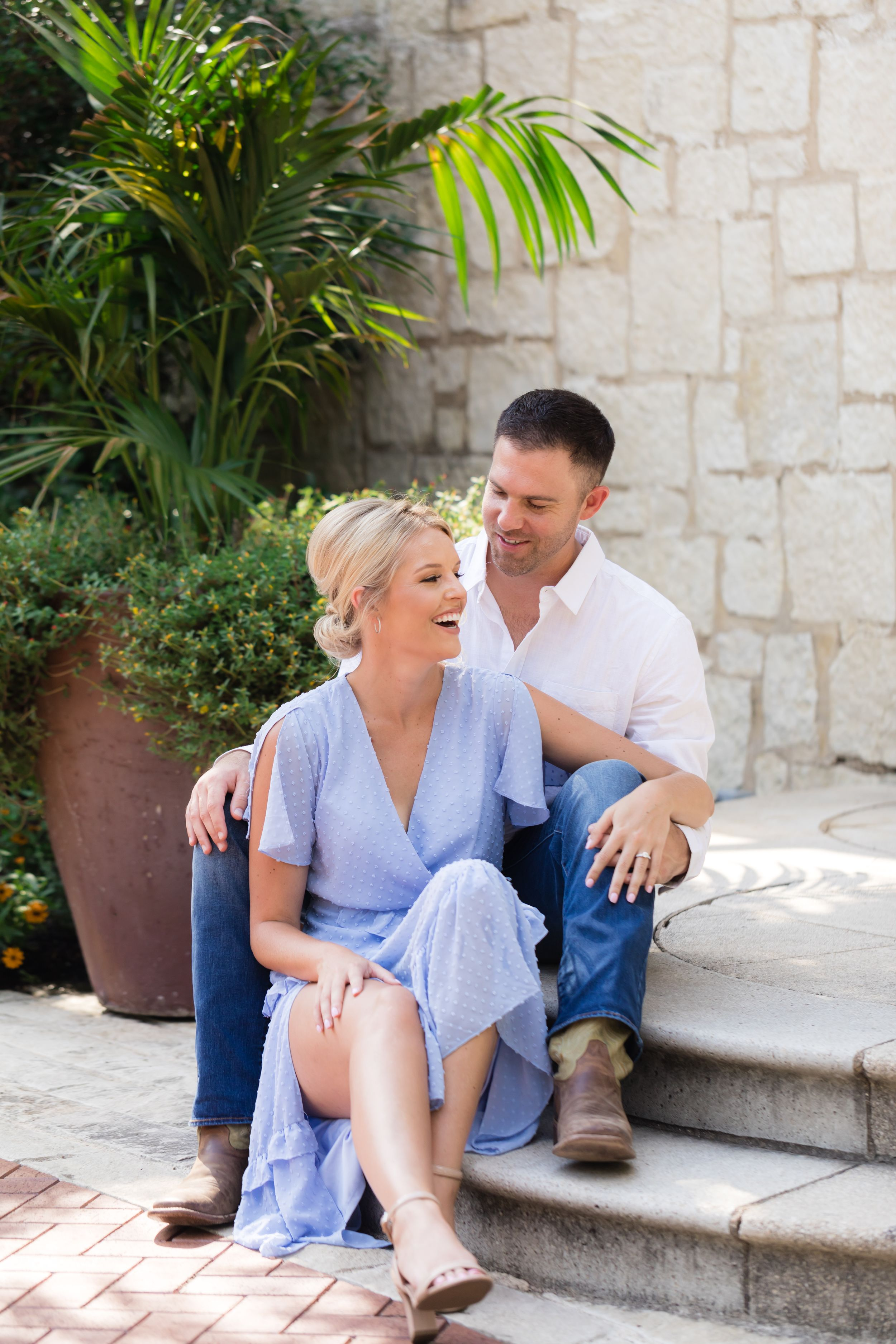 An engaged couple laughs on the stone steps at the Dallas Arboretum.