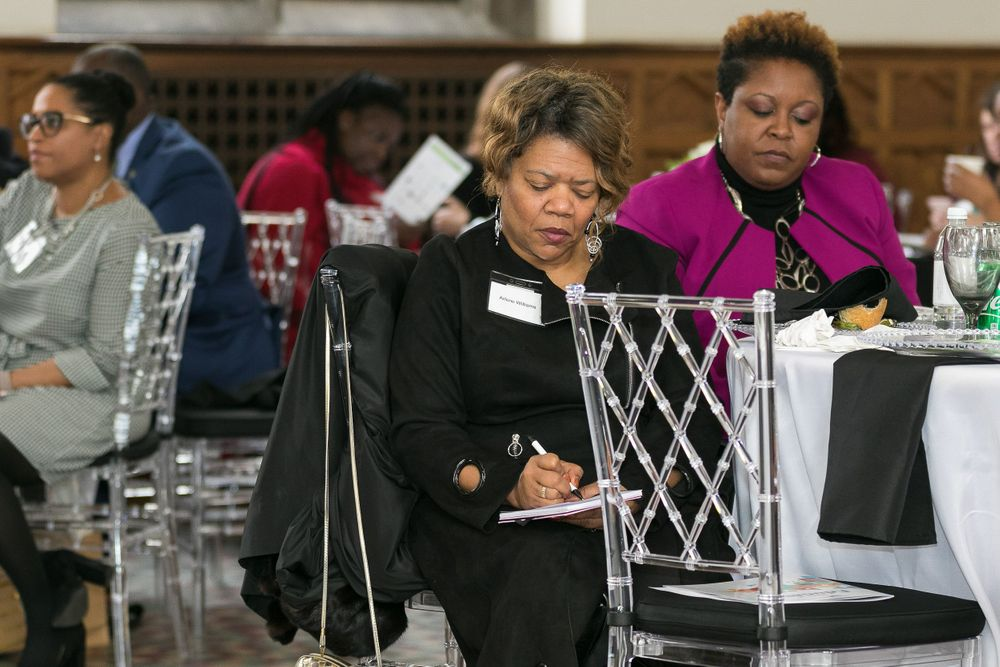 Black woman taking notes while at the table listening to the speaker.