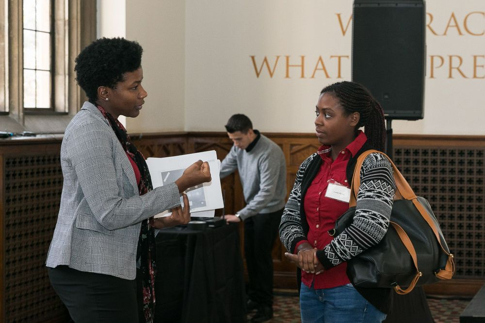 DCAN staff speaking with a luncheon attendee.
