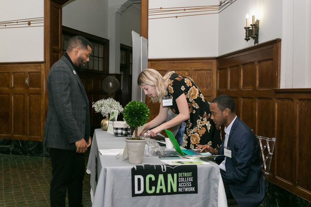 DCAN staff checking in a luncheon attendee at the table.