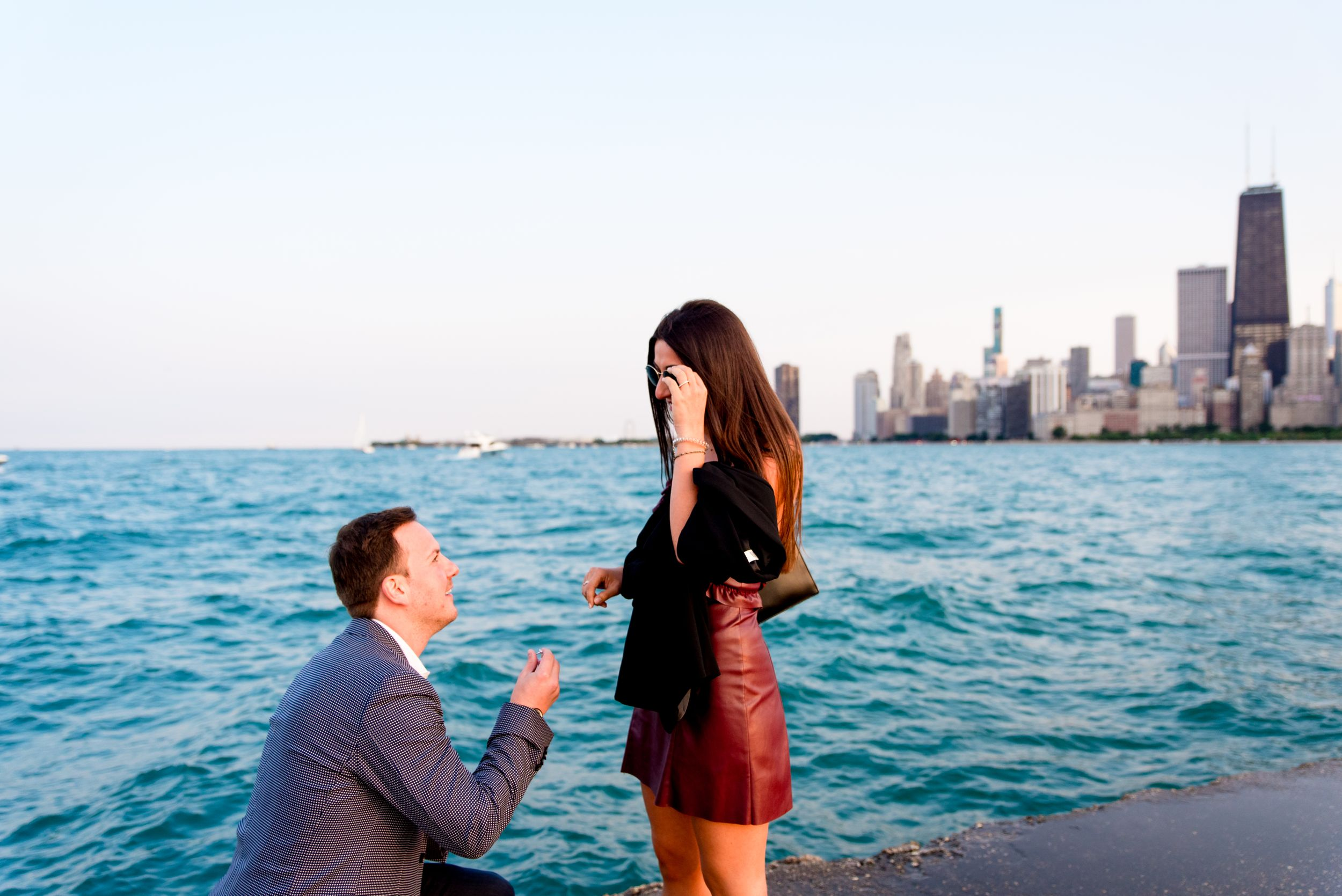 man in gray suit down on one knee for North Avenue Beach Chicago proposal