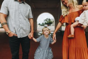 Small blonde girl in gingham dress plays between mom and dad while baby sister looks in Historic Fayetteville NC