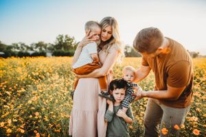 South African couple cuddle and play with their three boys in a flower field in Raleigh North Carolina