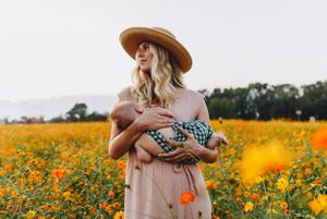 Mom breastfeeds her young babe in a field of orange and yellow flowers in Four Oaks NC