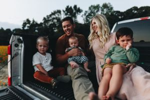 Parents hold their three boys in the back on their truck lit by the sunset in Raleigh North Carolina