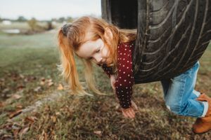 red headed toddler swings on tire swing on family farm