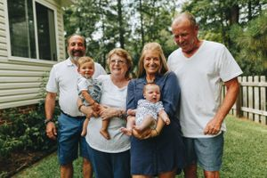 Grandparents hold their two youngest grandbabies in a natural light photo taken in Carolina Lakes