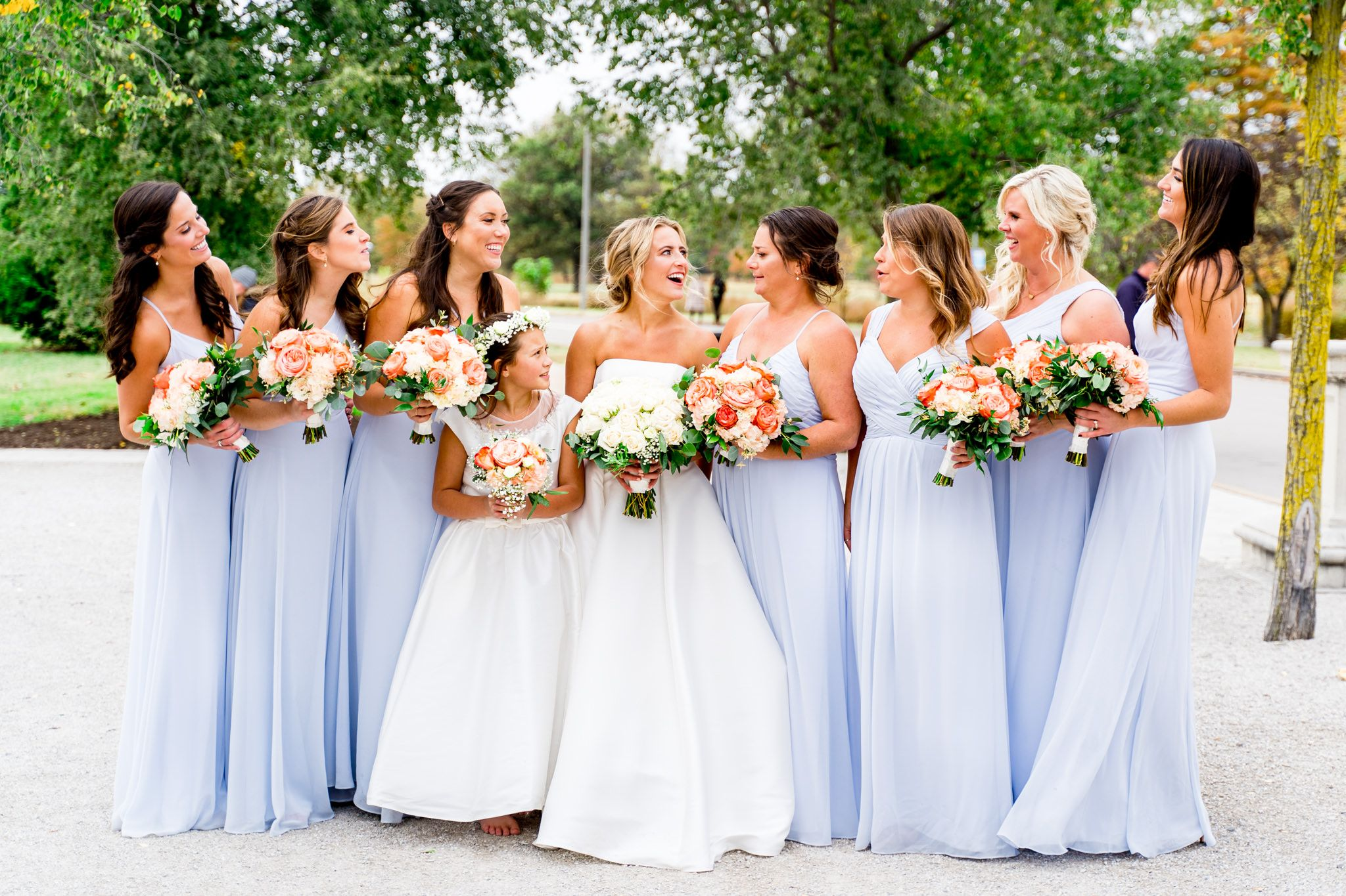 bride laughs with bridesmaids in light blue dresses and coral bouquets at STL Forest Park fall wedding