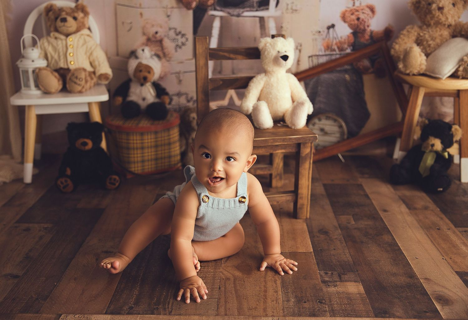 happy baby boy sitting on wood floor