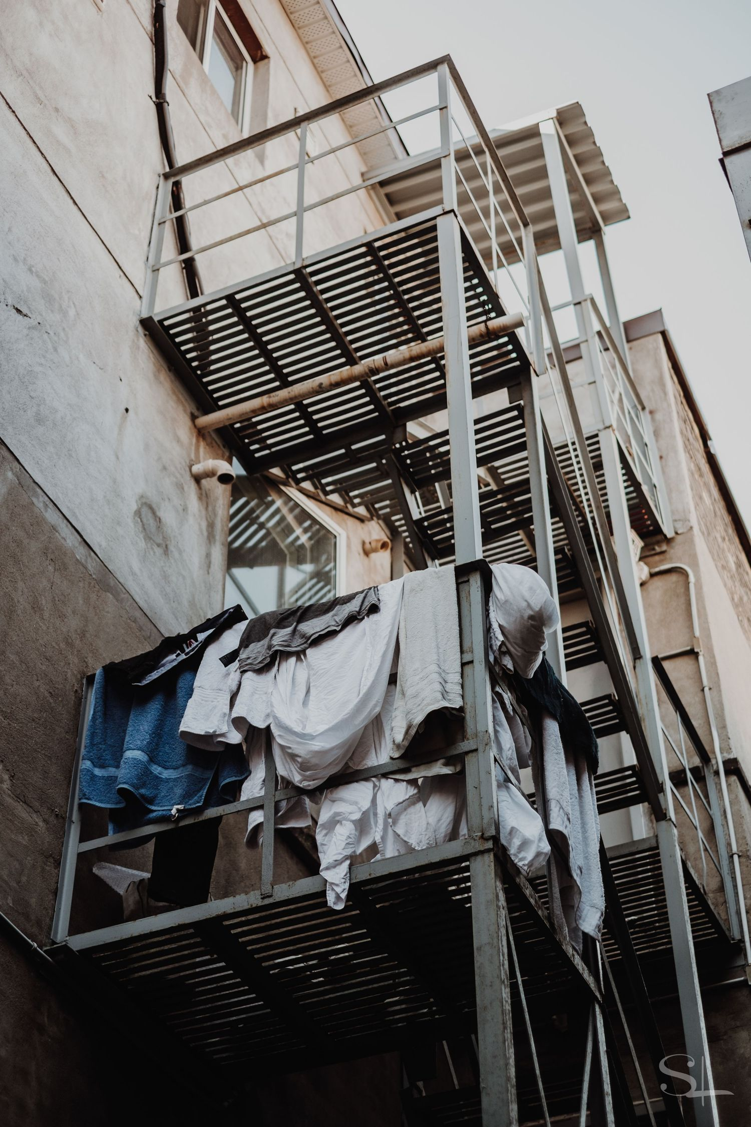 laundry hangs from a back alley fire exit