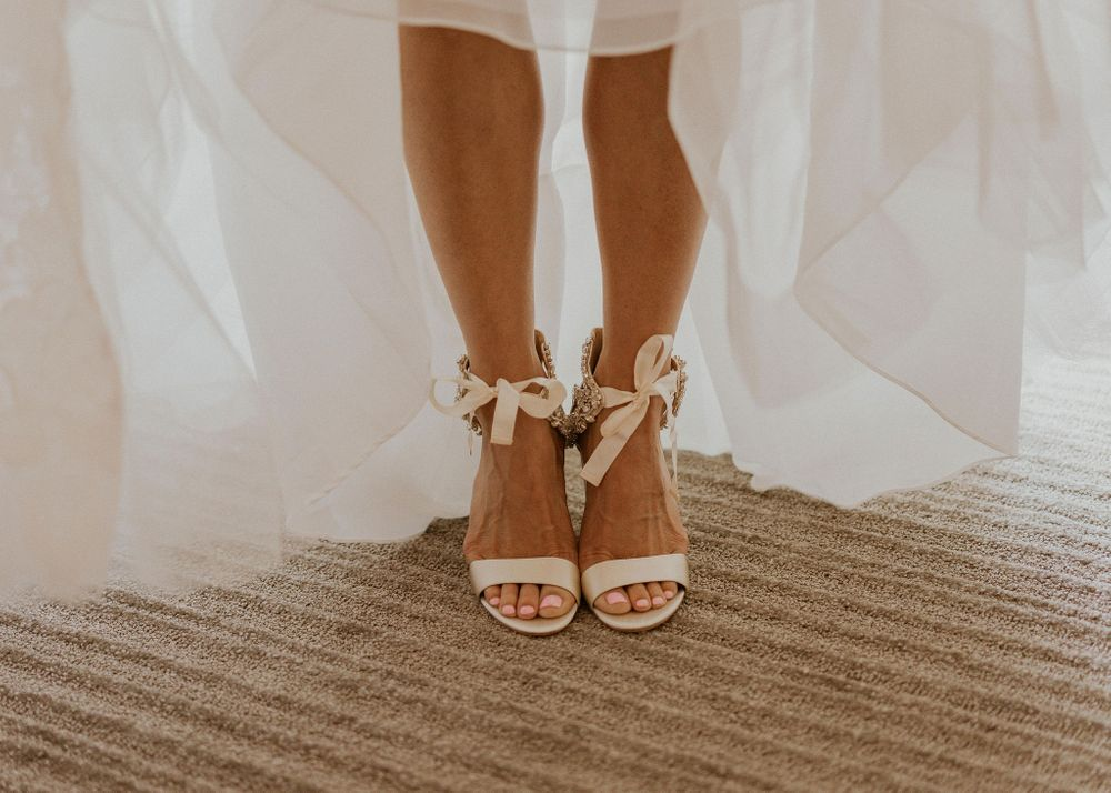 Bride showing off her shoes under the skirt of her dress
