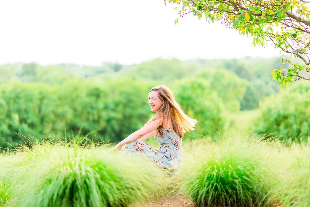 Chicago Senior girl sitting sideways in a field of green grass flipping her hair and smiling laughing