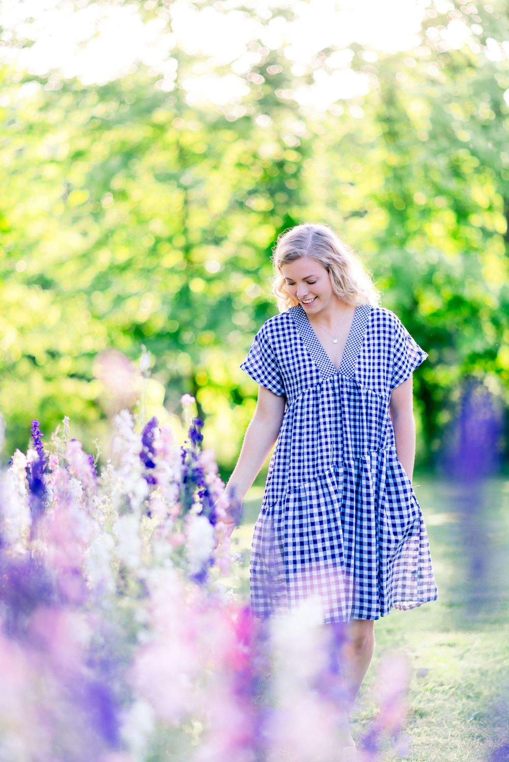 blonde girl in blue and white checkered dress walking through a field of purple, pink, and white flowers in summertime