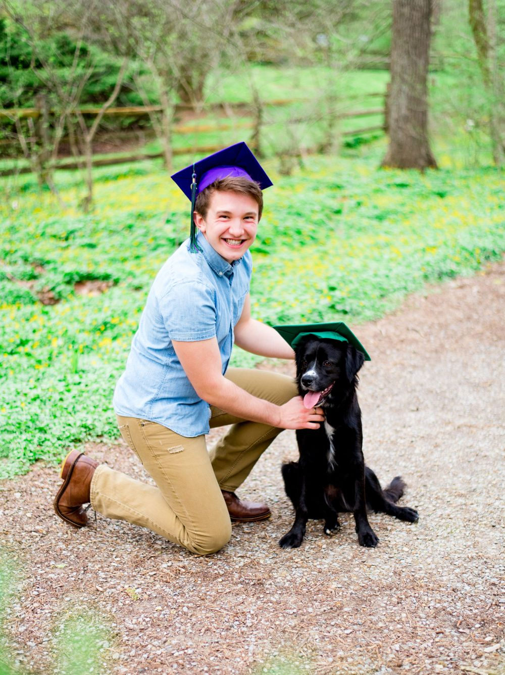 high school senior boy in denim shirt and khaki pants and a graduation cap kneeling to pet his dog in a graduation cap