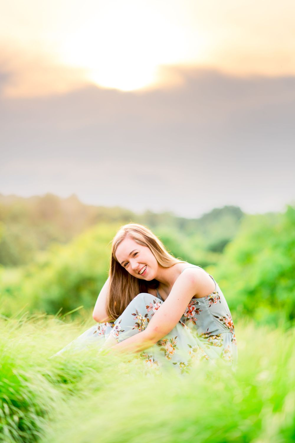 girl in a light blue floral dress sitting and leaning on her knee in a field of light green grass with a purple sky