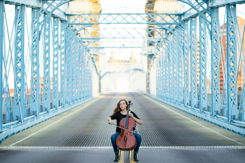 senior girl playing cello in the middle of Cincinnati's blue Roebling Bridge