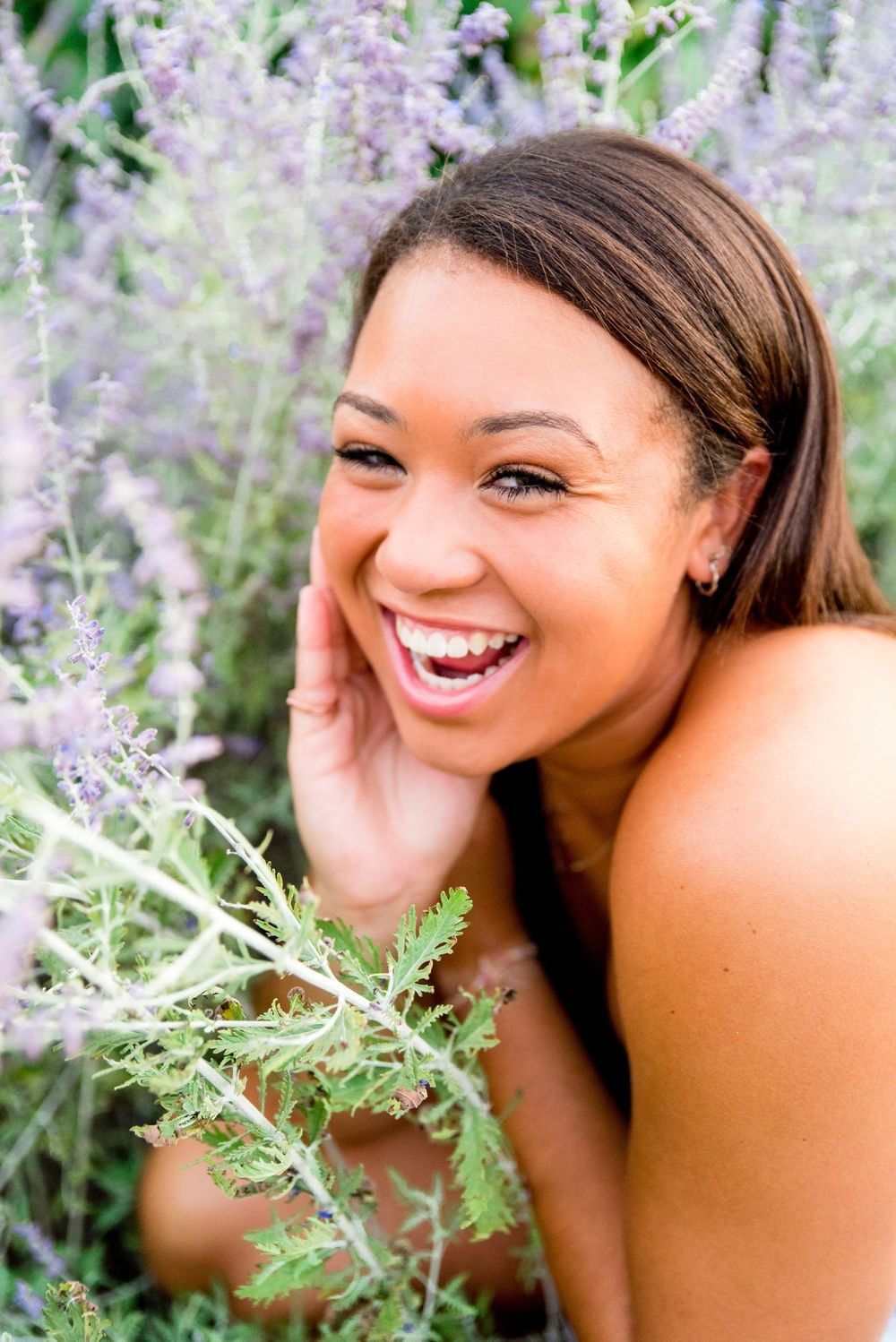 girl with shoulder length brown hair smiling and laughing in a field on lavender