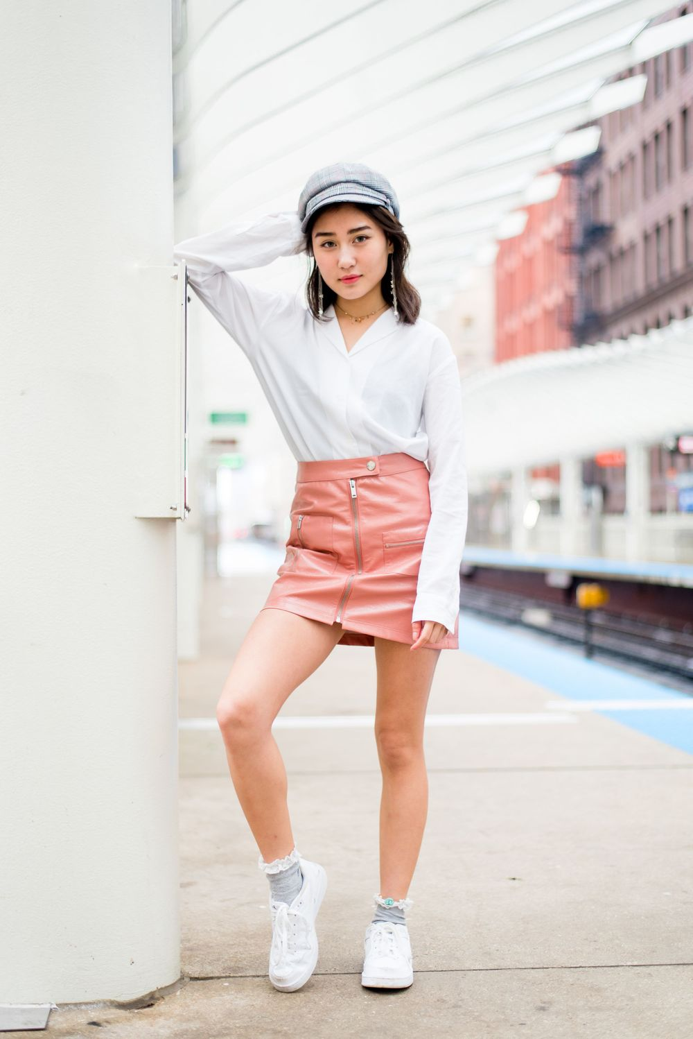 Asian girl in a light pink vinyl skirt and white blouse leaning her elbow against the wall at the Chicago L station