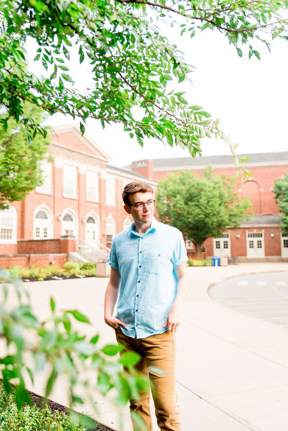 High School senior boy in blue shirt and khaki pants wearing glasses outside looking to the right by a tree