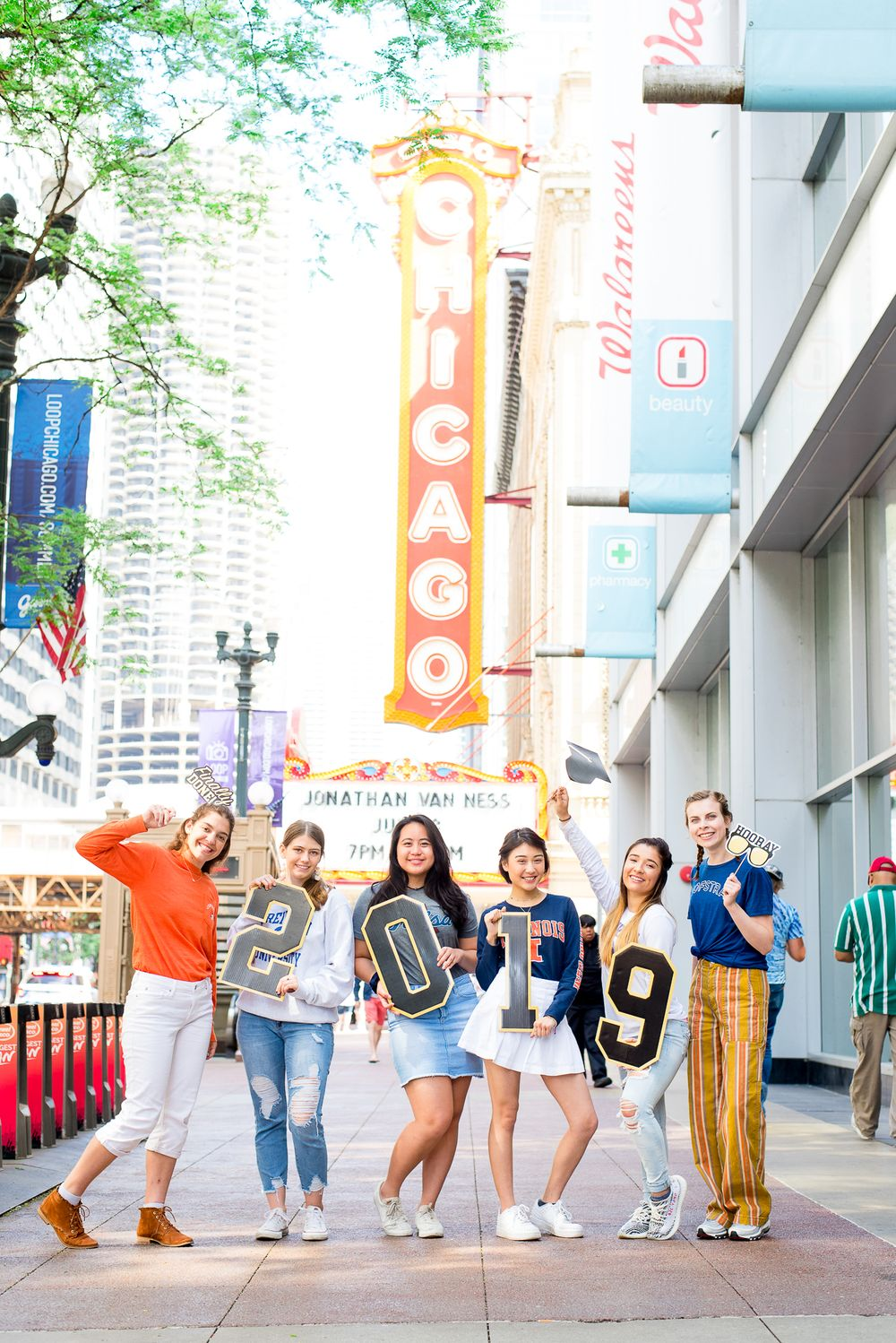 "six senior girls holding up numbers ""2019"" by the Chicago Theater in downtown Chicago loop"
