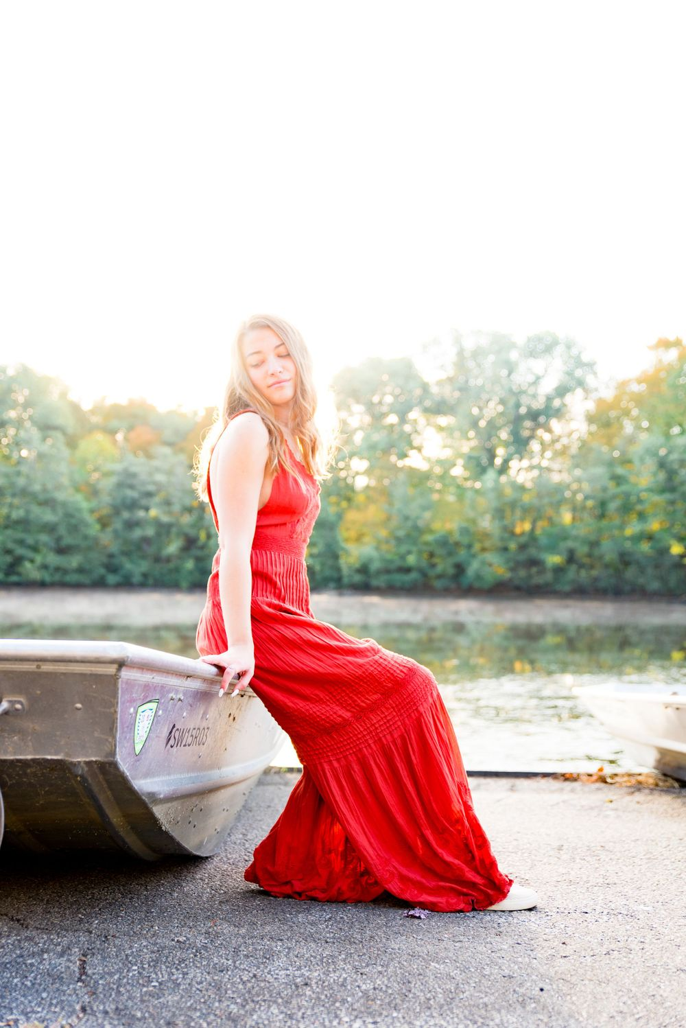 high school girl in a bright orange wide leg jumpsuit sitting on the edge of a silver canoe next to a pond at sunrise