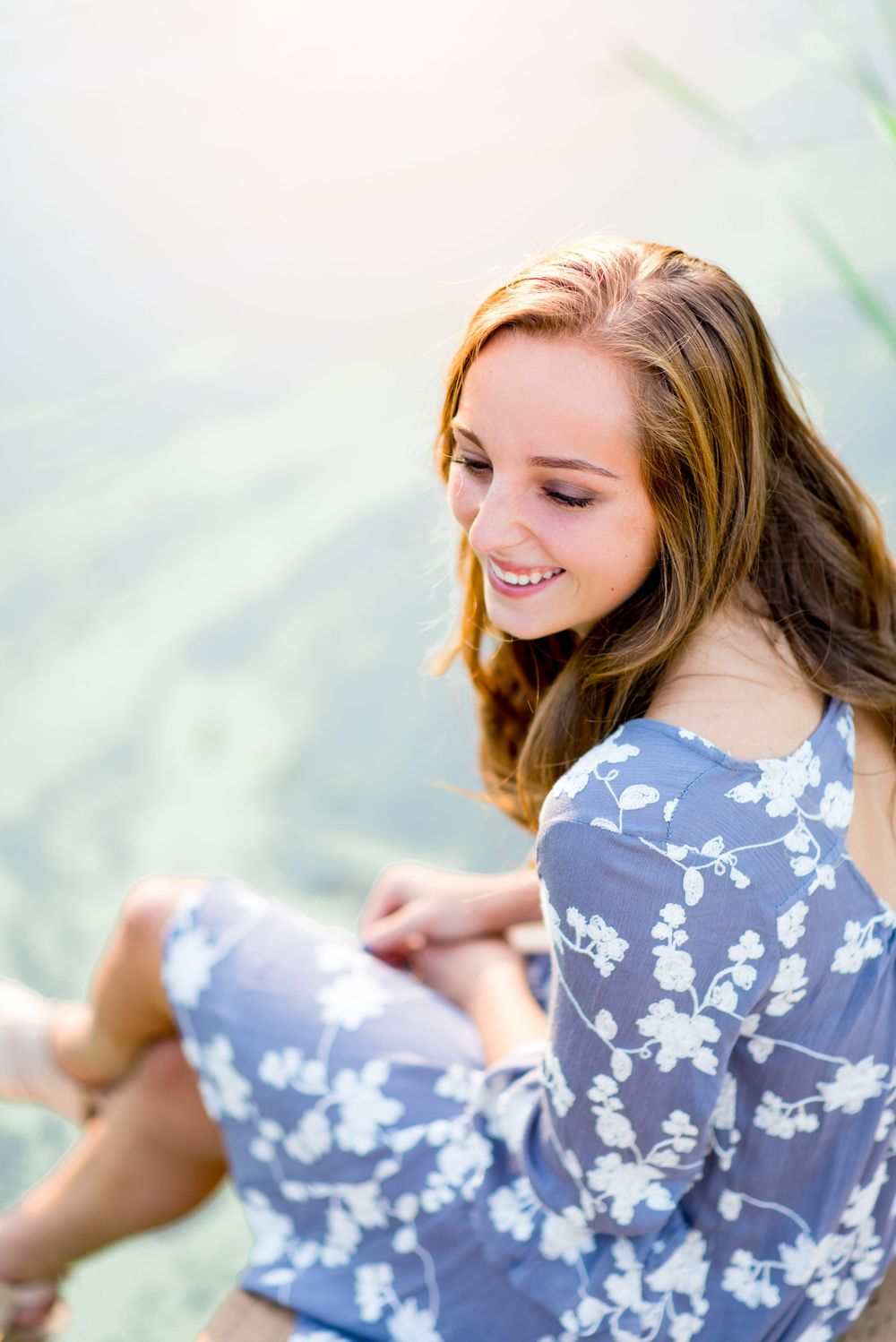 young girl in a periwinkle floral dress sitting on a dock at a pond smiling and looking to the side