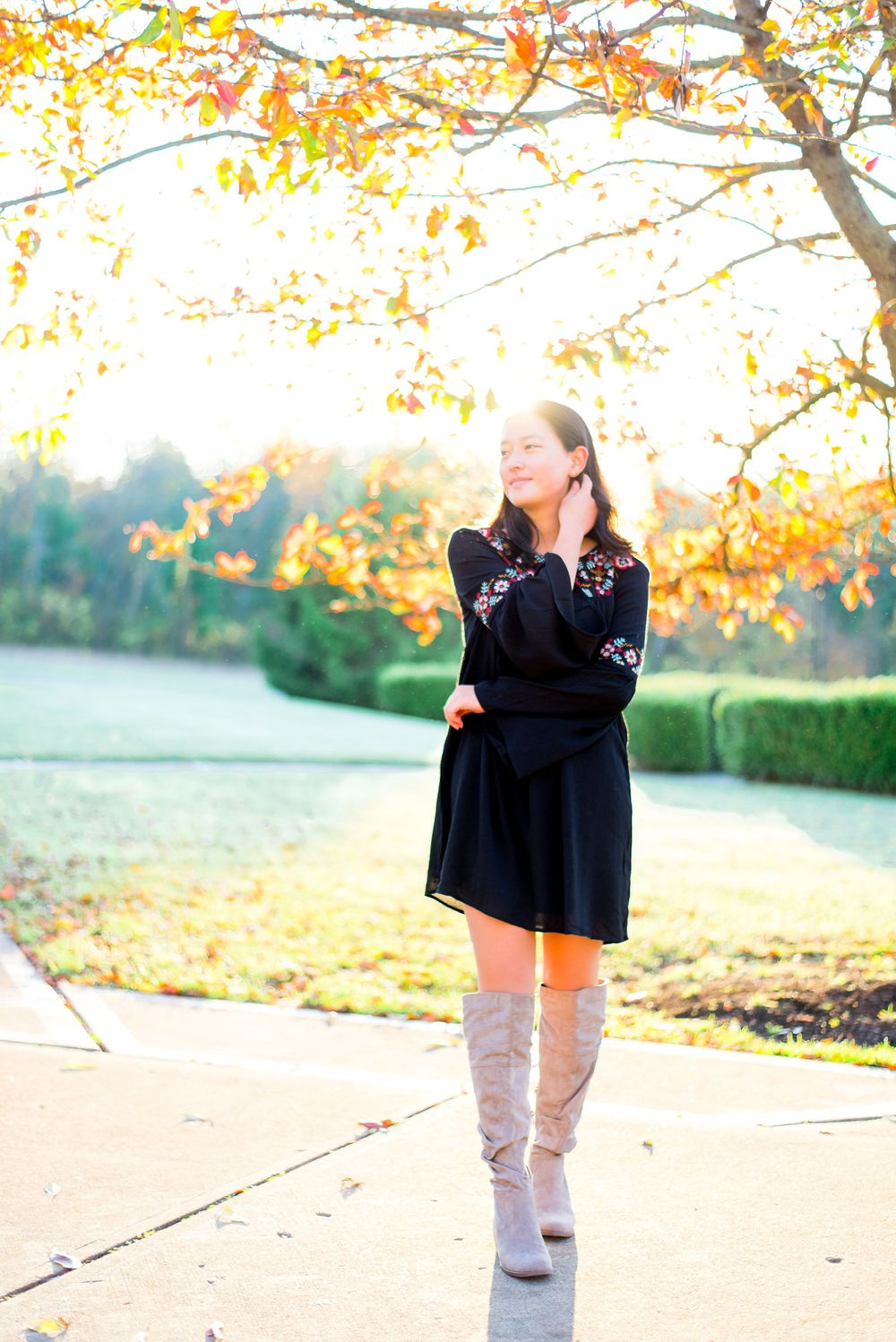 girl in black long sleeve dress and over the knee gray boots crossing arms in front of a yellow tree at sunrise