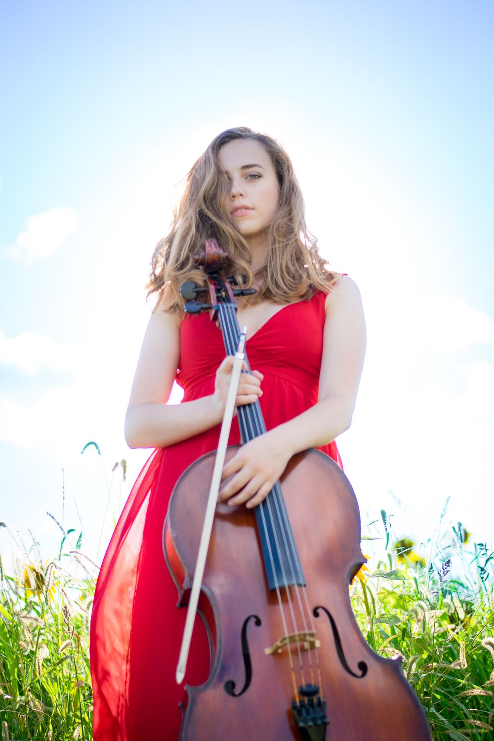 young girl in red dress with cello standing in a sunflower field with a blue sky and sun behind her