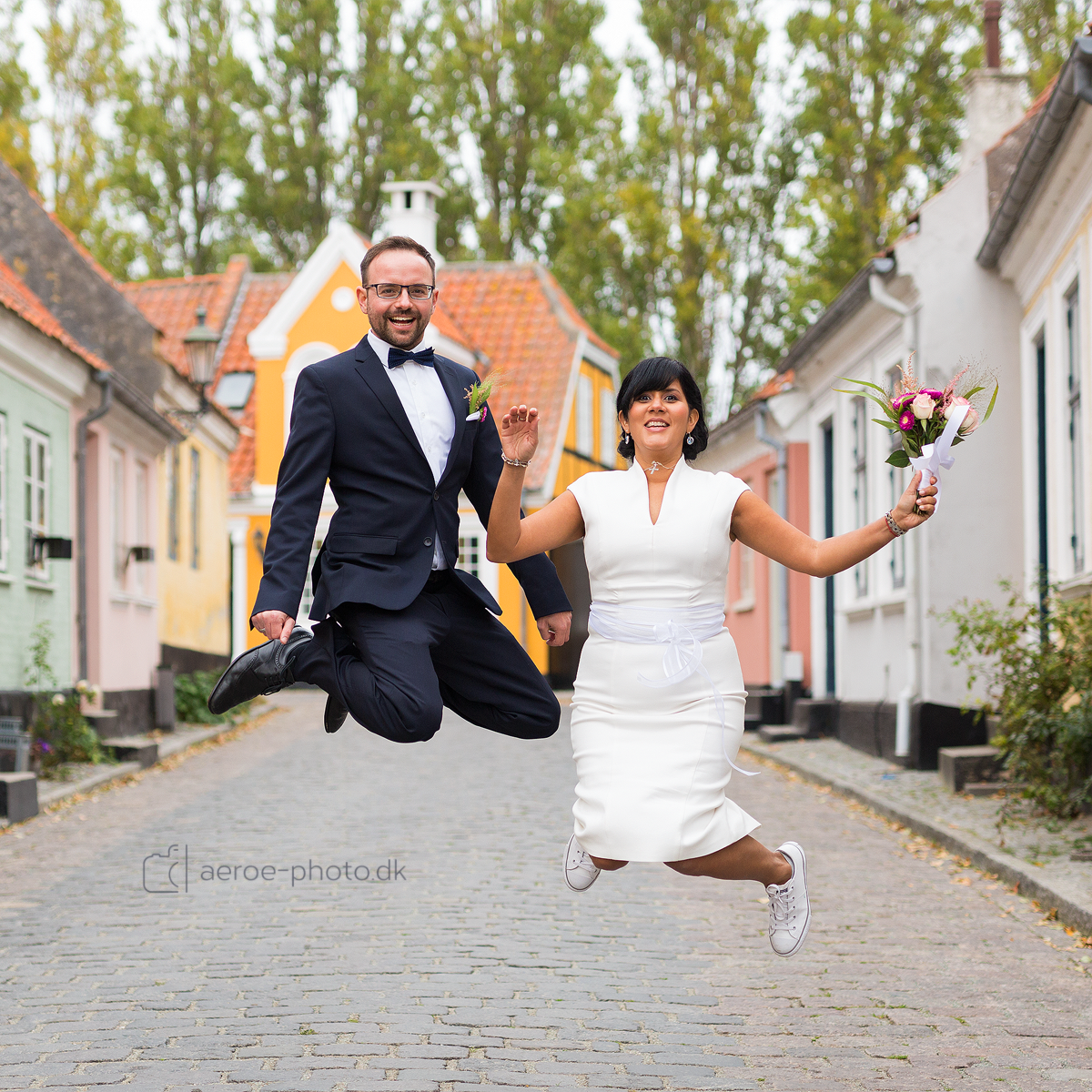 Wedding couple jumping high in the streets on the island Ærø.