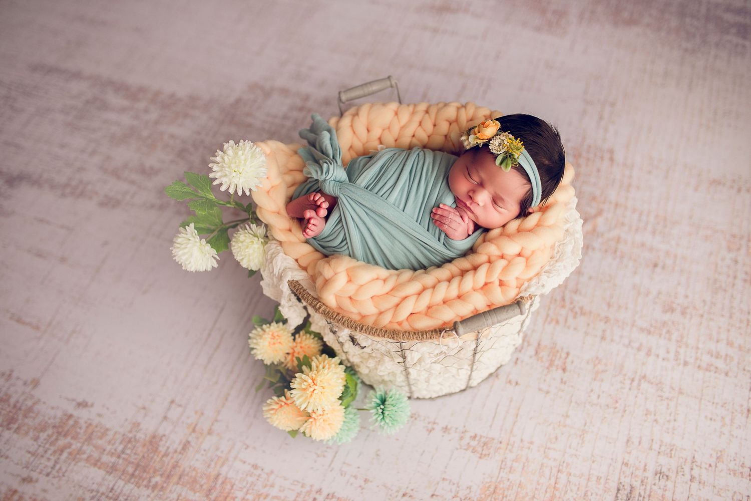 newborn baby girl in a basket wrapped in teal flowers