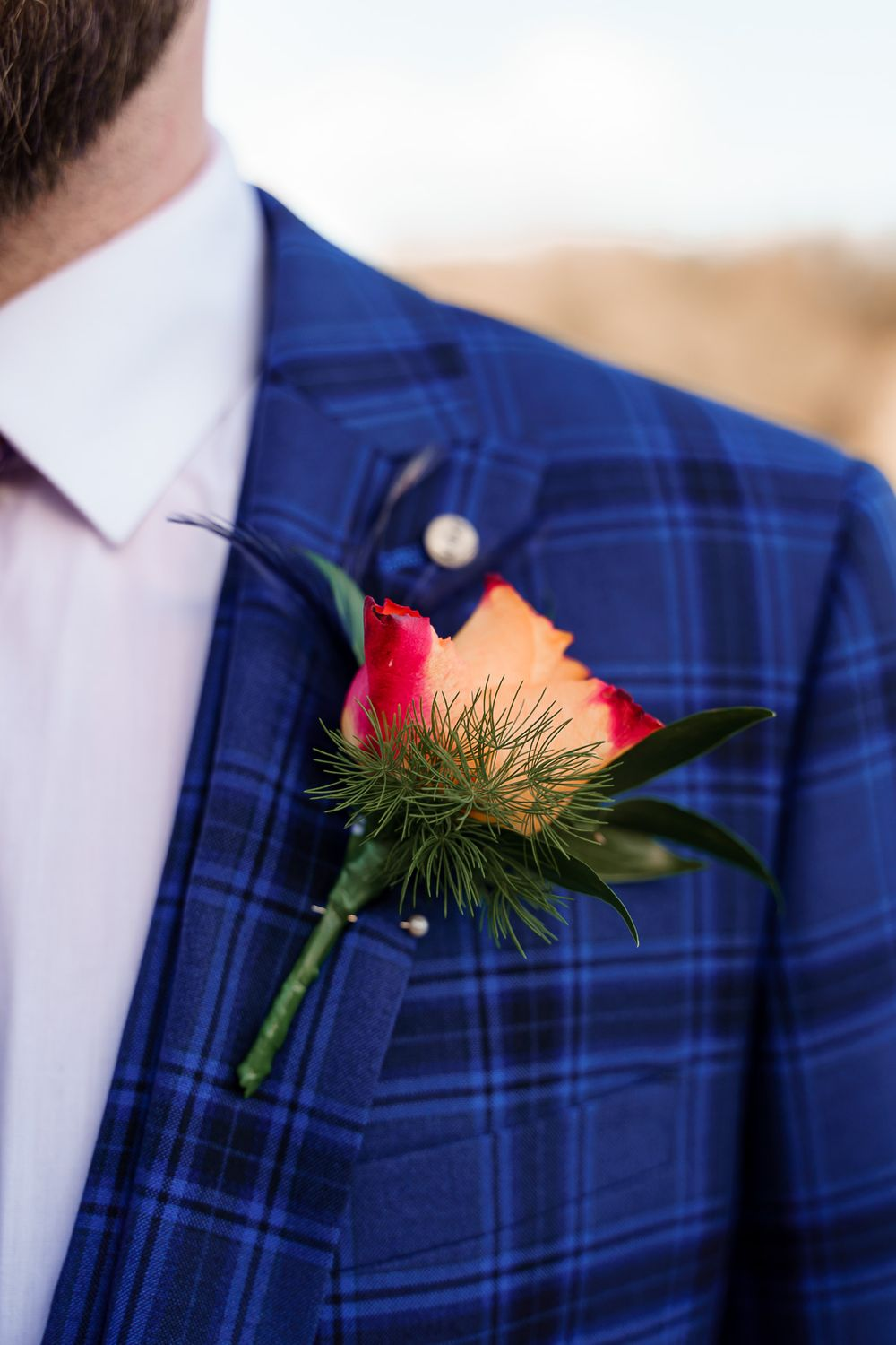 Colourful red and orange rose buttonhole against a bold blue check suit - peacock wedding theme Winchester