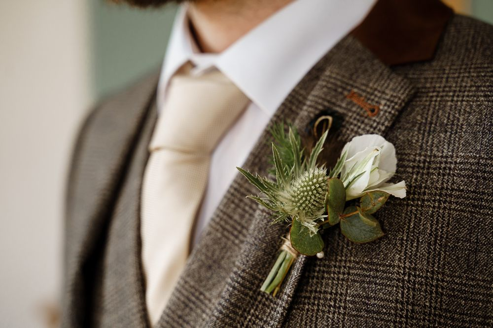 Green and white buttonhole on a groom's lapel - Winchester wedding photography