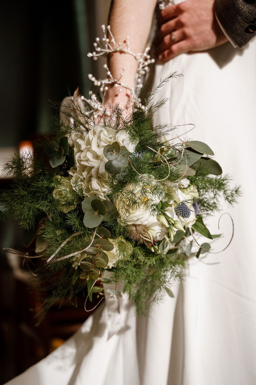 Bride holds a green and white bouquet by her side - Winchester wedding photography