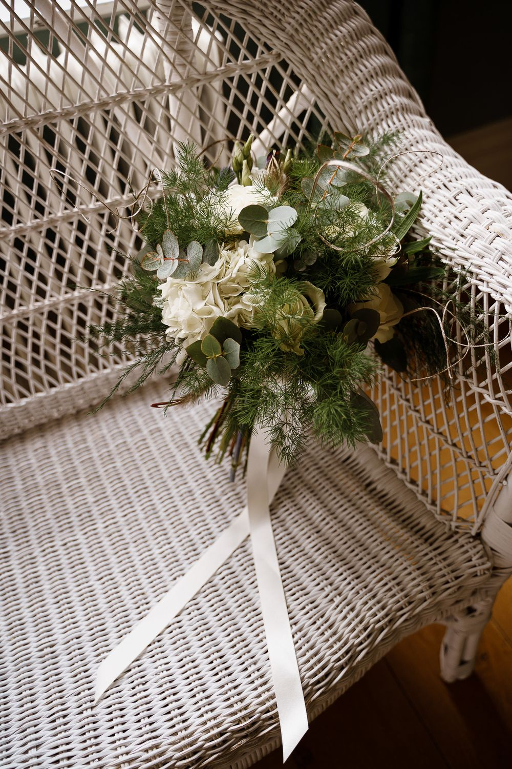 Green and white wedding bouquet on a white wicker chair - Winchester wedding photography