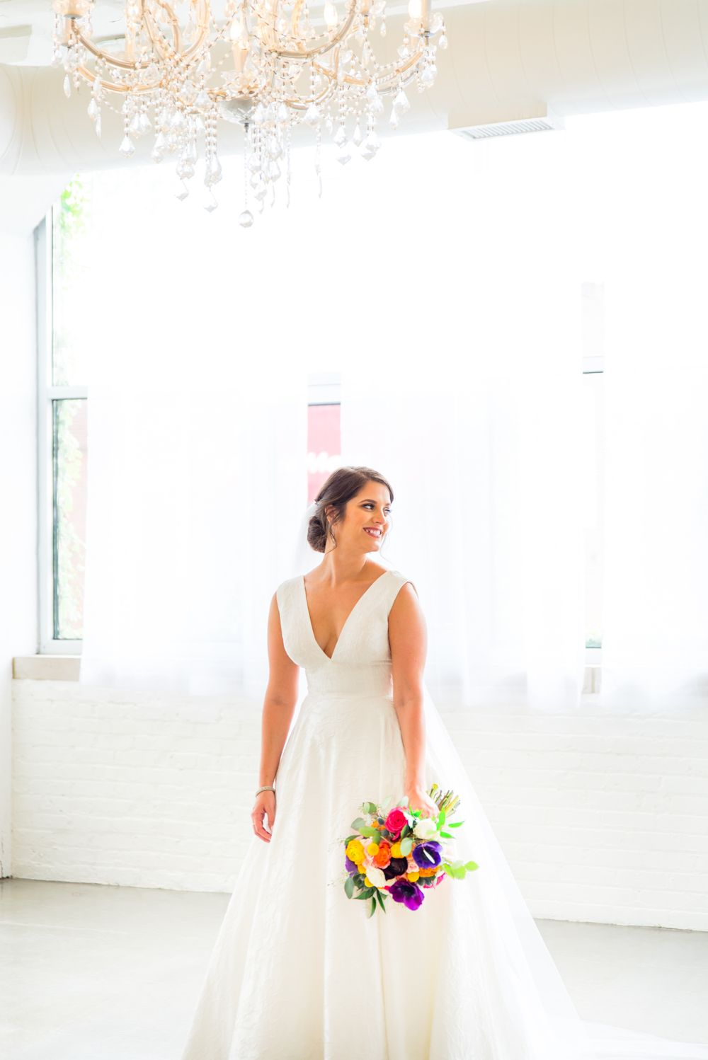 bride with colorful bouquet smiling in all white Room 1520 Chicago Wedding Venue