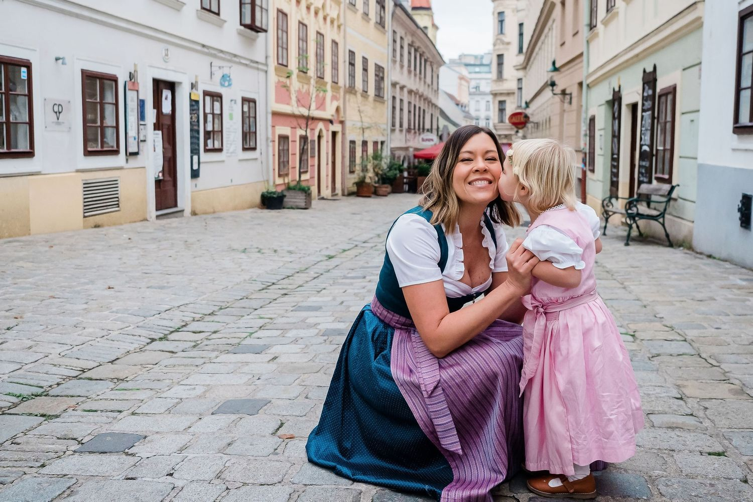 Mother and daughter in a street in Vienna wearing traditional outfit Dirndl