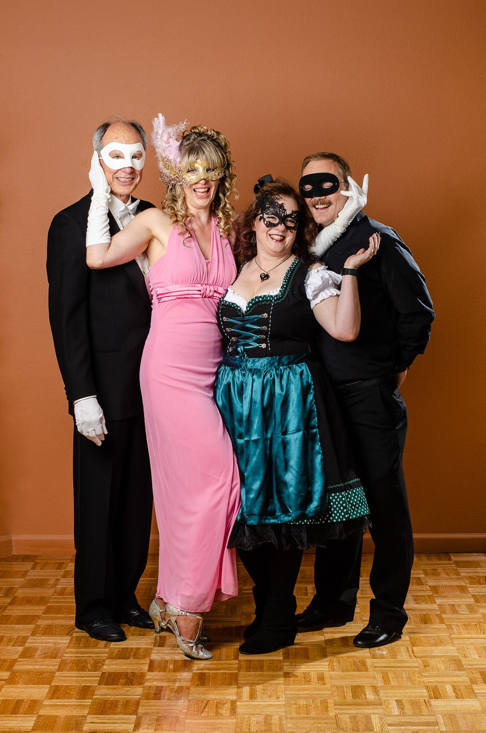Two couples in costume posing against a wall.