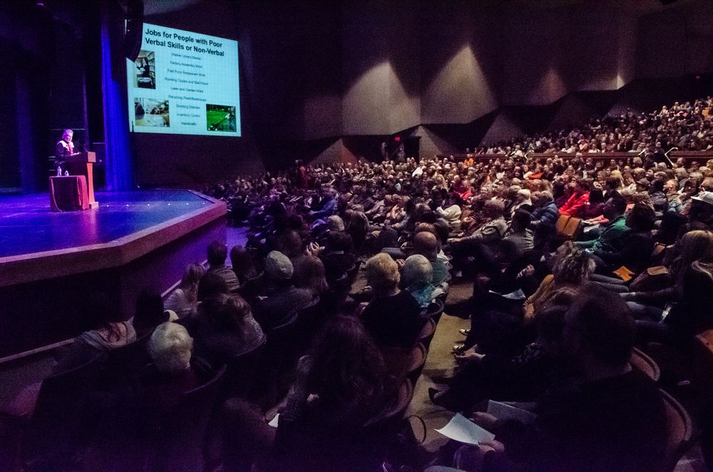 Picture of autistic celebrity Temple Grandin speaking on stage in front of a packed auditorium.