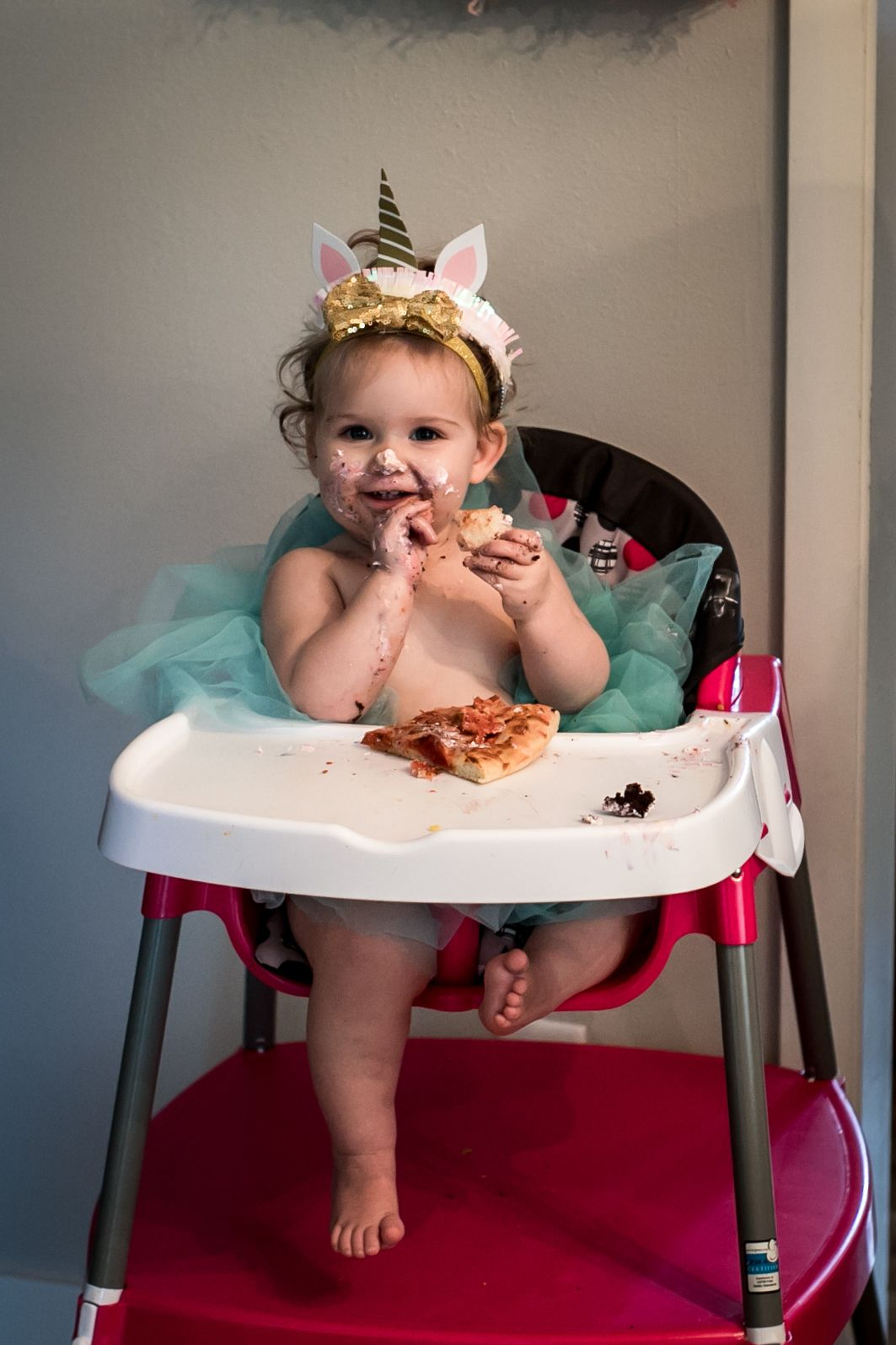 One year old enjoying a piece of pizza on her 1st birthday in Sioux City, Ia.