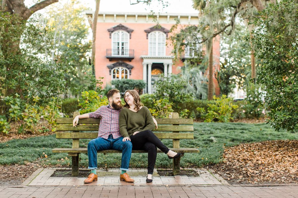 downtown savannah engagement session with couple sitting on bench in monterey square