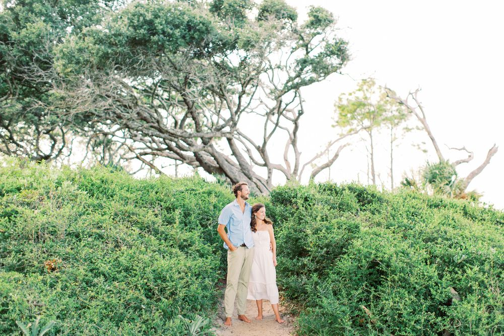couple posing in the bushes and trees in driftwood beach in Jekyll Island, GA