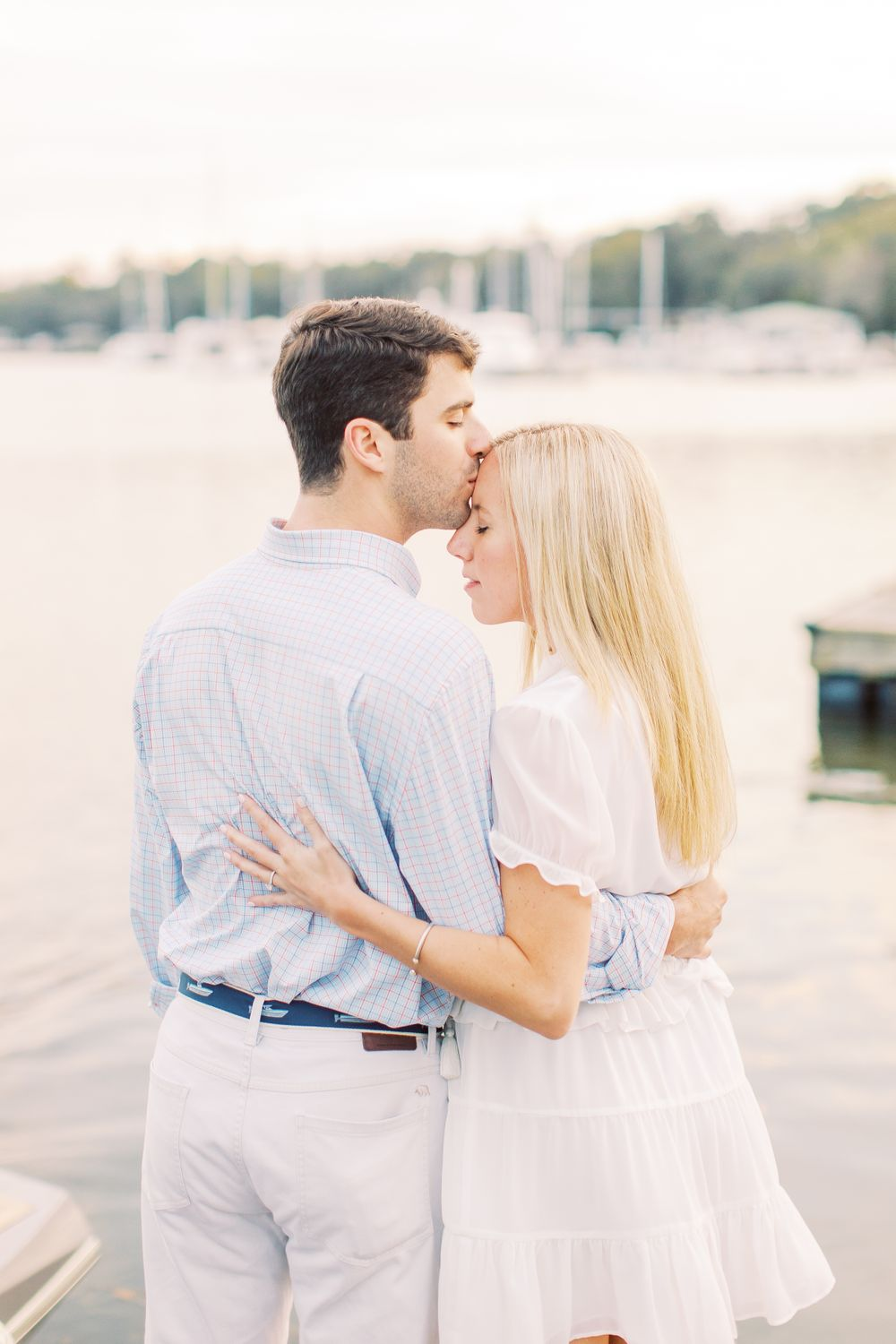 man kissing woman on the forehead while they hug in front of the water in savannah, ga