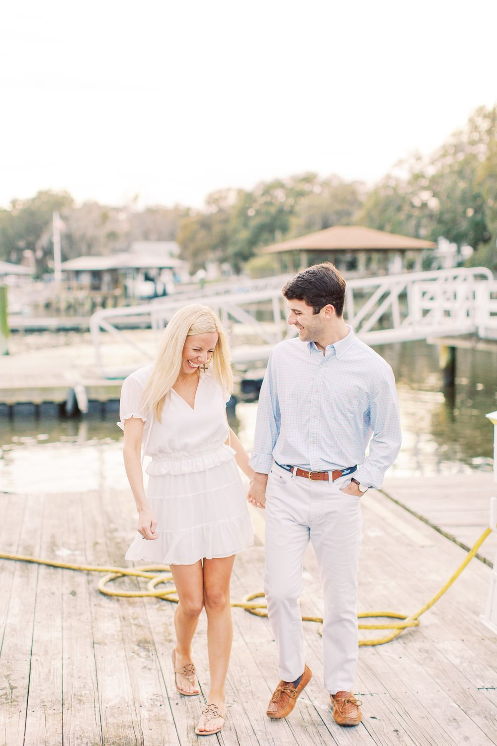 couple holds hands and walks on a dock near the water in isle of hope