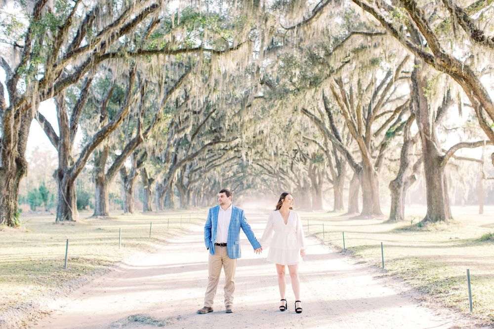 couple holds hands and look away from each other while posing for their engagement session in wormsloe